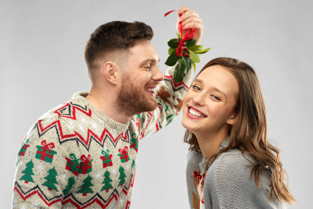 happy couple kissing under the mistletoe stock photo