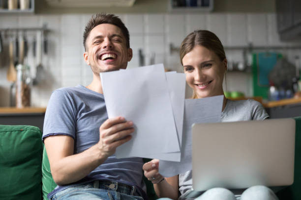 happy couple laughing having fun with documents and laptop - bills couple imagens e fotografias de stock