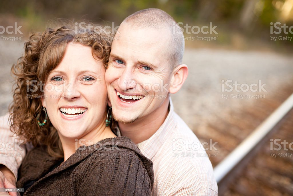 Happy Couple Laughing Together Outside By Railroad Tracks royalty-free stock photo