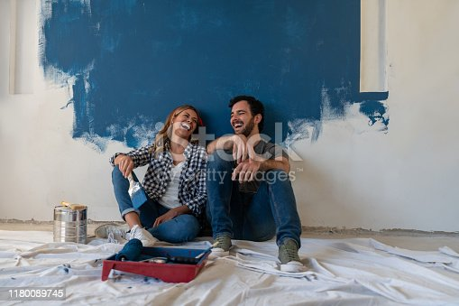 Portrait of a happy couple laughing while taking a break from painting - home improvement concepts