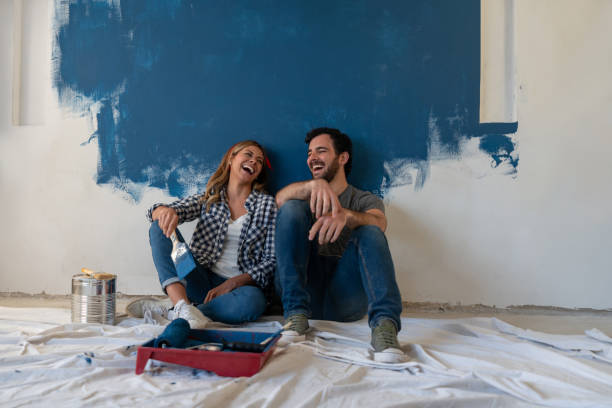 happy-couple-laughing-while-taking-a-break-from-painting-picture-id1180089745?k=6&m=1180089745&s=612x612&w=0&h=zqiTxoBx5a4ay6kY703rWZ3TBnlj1aapAXn-NZV2kUQ=