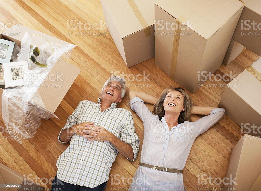 Glückliches Paar Leg dich mit dem Rücken auf dem Boden eines neuen Hauses - Lizenzfrei 55-59 Jahre Stock-Foto