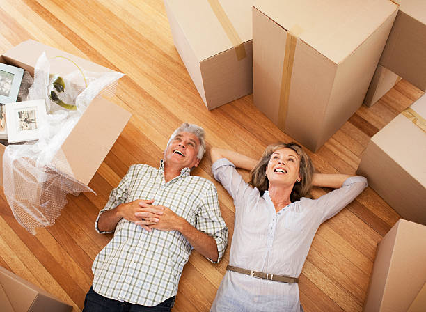 Happy couple laying on floor of new house stock photo