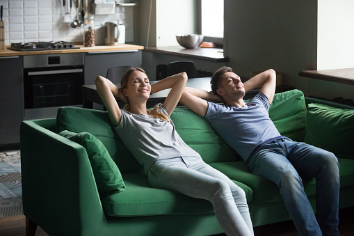 973962076 istock photo Happy couple leaning on sofa together, stress free weekend concept 1028900558