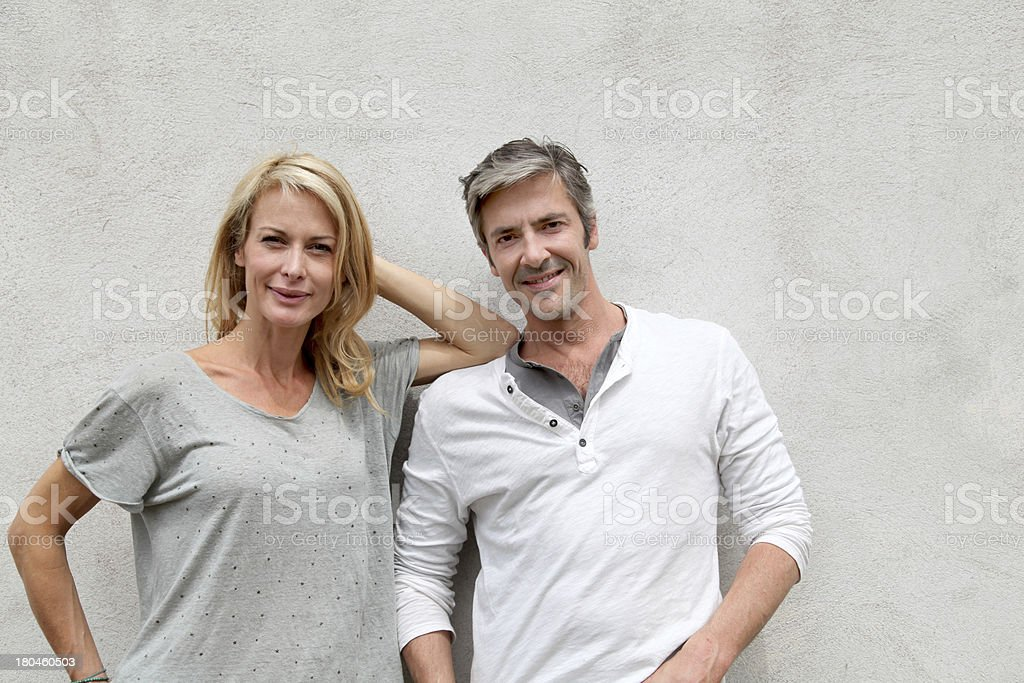 Happy couple leaning on wall and looking at camera royalty-free stock photo