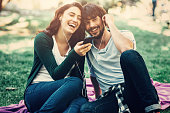 Young happy couple sitting on a blanket and listening to music outdoors.