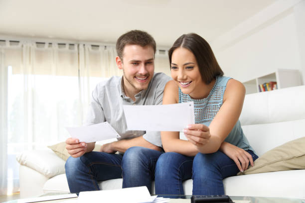 Happy couple looking and checking bills at home stock photo