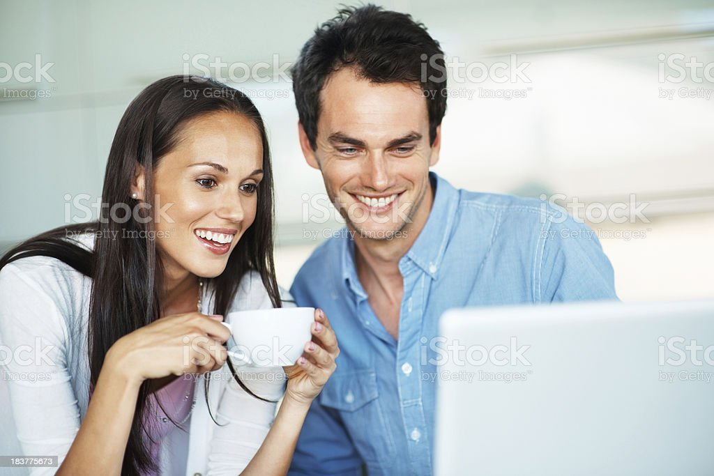 Happy couple looking at laptop royalty-free stock photo