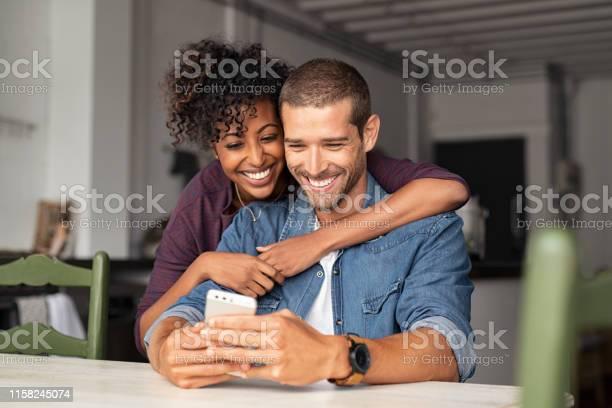 Pareja Feliz Mirando El Teléfono Juntos Foto de stock y más banco de imágenes de 20 a 29 años