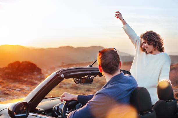 Happy couple looking at sunset from convertible stock photo