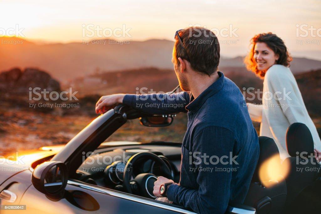 Glückliches Paar Blick auf Sonnenuntergang vom Cabriolet – Foto