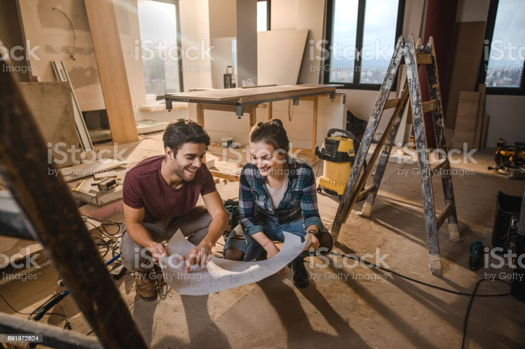 Happy couple looking at their housing project on construction site. stock photo