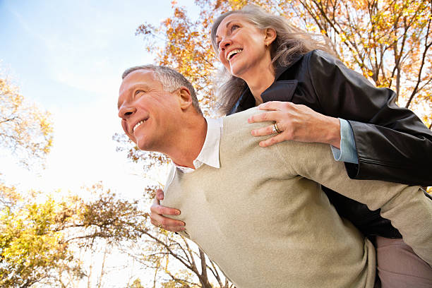 Happy Couple Looking Forward Together With Beautiful Trees in Background stock photo