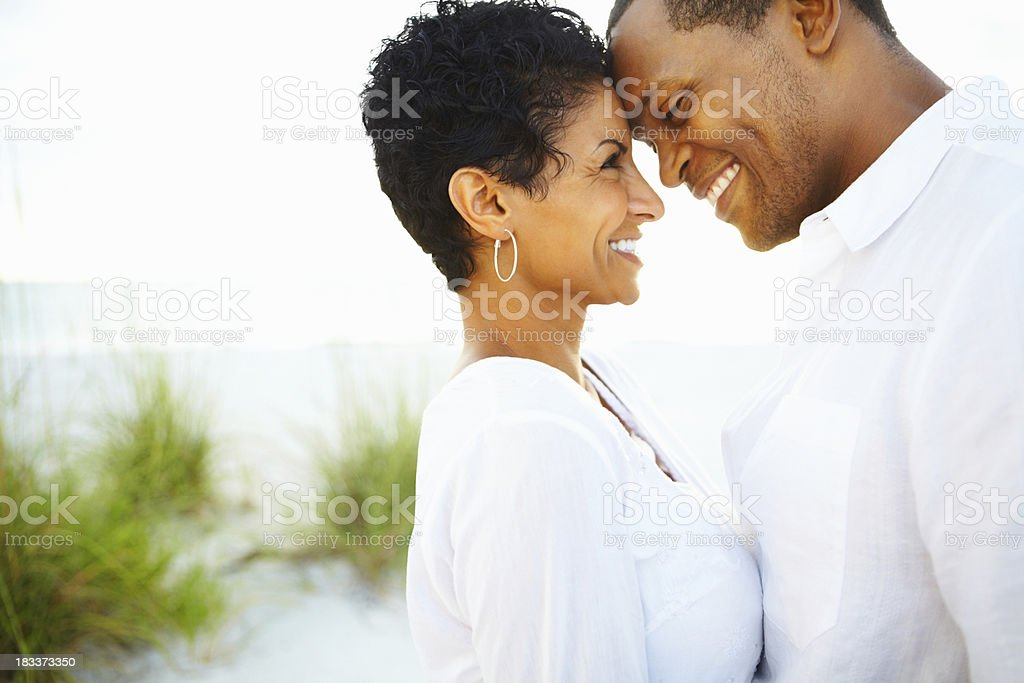Happy couple looking into each others eyes along the shoreline stock photo