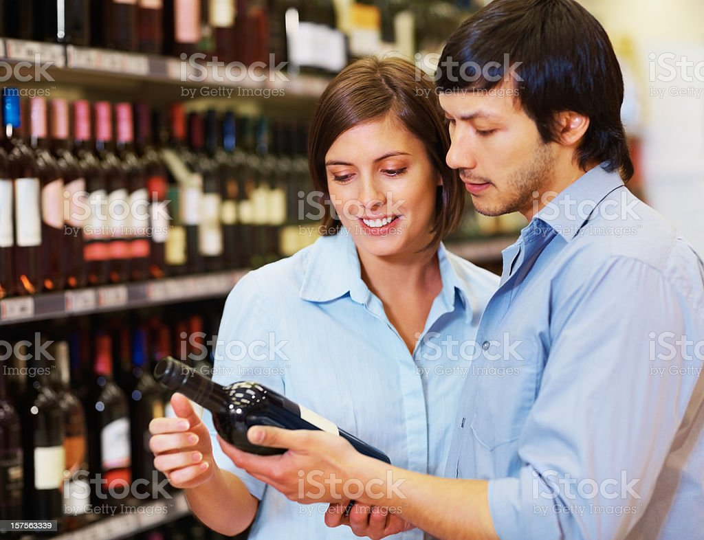 Happy couple looking out for a wine bottle at supermarket royalty-free stock photo