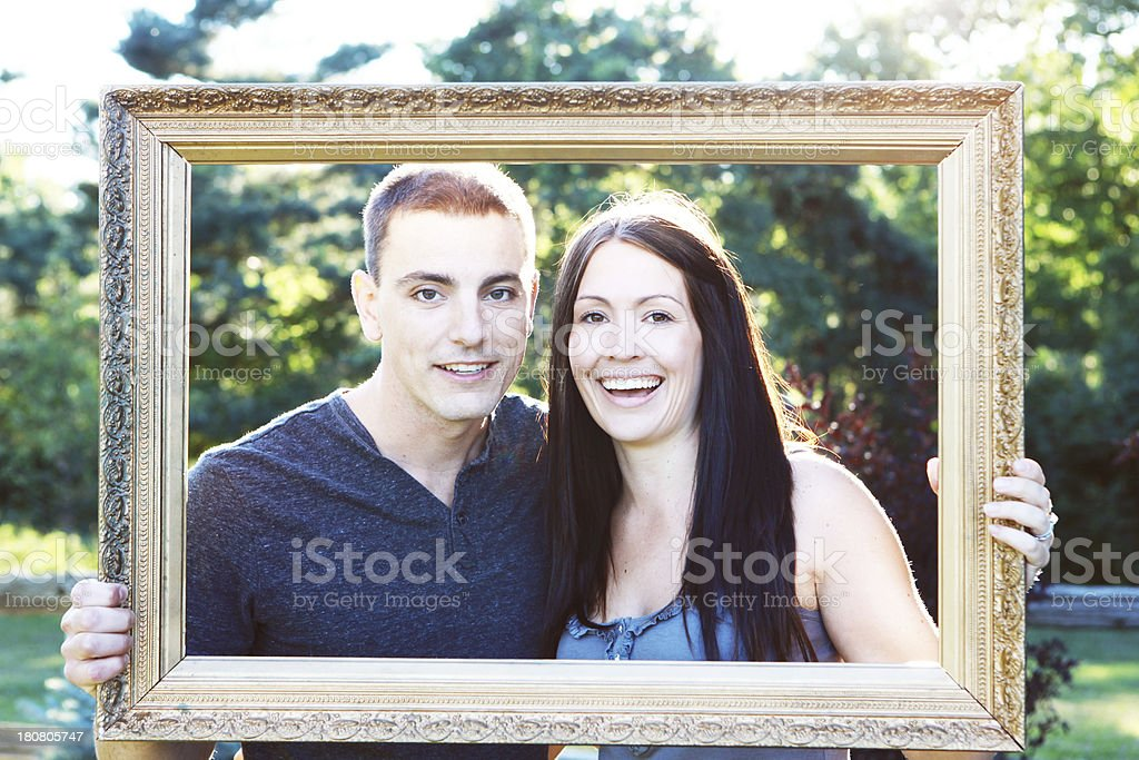 Happy Couple Looking Through Picture Frame royalty-free stock photo
