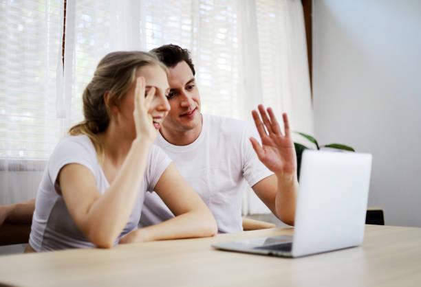 happy par älskare talar och viftade hand i en videokonferens på nätet med en bärbar dator för kontakt vänskap hemma. - video call bildbanksfoton och bilder