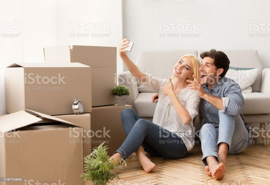 Excited Couple Making Selfie Among Moving Boxes Sitting On Floor In...