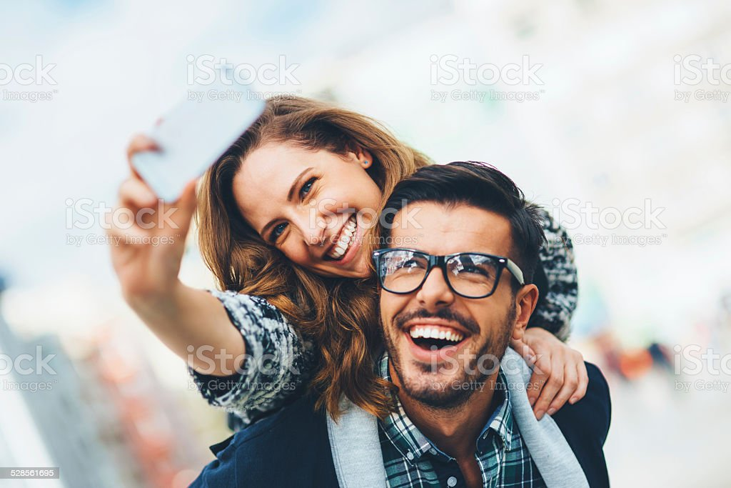 Happy couple making selfie outdoors stock photo
