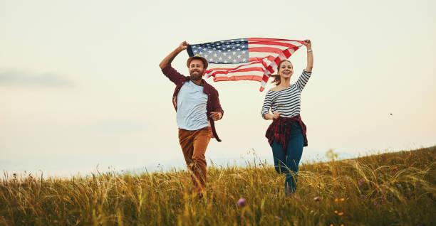happy couple man and woman with flag of united states enjoying t - family 4th of july zdjęcia i obrazy z banku zdjęć
