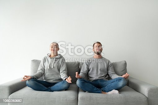 1060280760 istock photo Happy couple meditate at home practicing yoga 1060280682