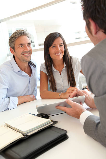 Happy couple meeting real estate agent in office stock photo