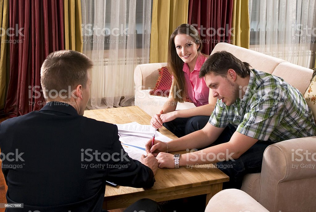 Happy couple meeting with agent at home royalty-free stock photo