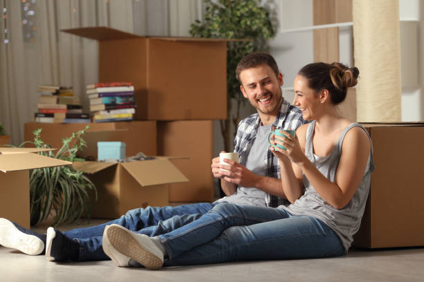 Happy couple moving home resting and talking stock photo
