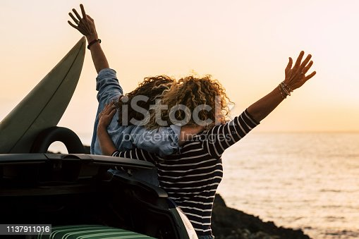 istock Happy couple of curly girl have fun together and look at the sunset in front of the ocean in tropical beautiful vacation outdoor - hug and friendship for happy people 1137911016