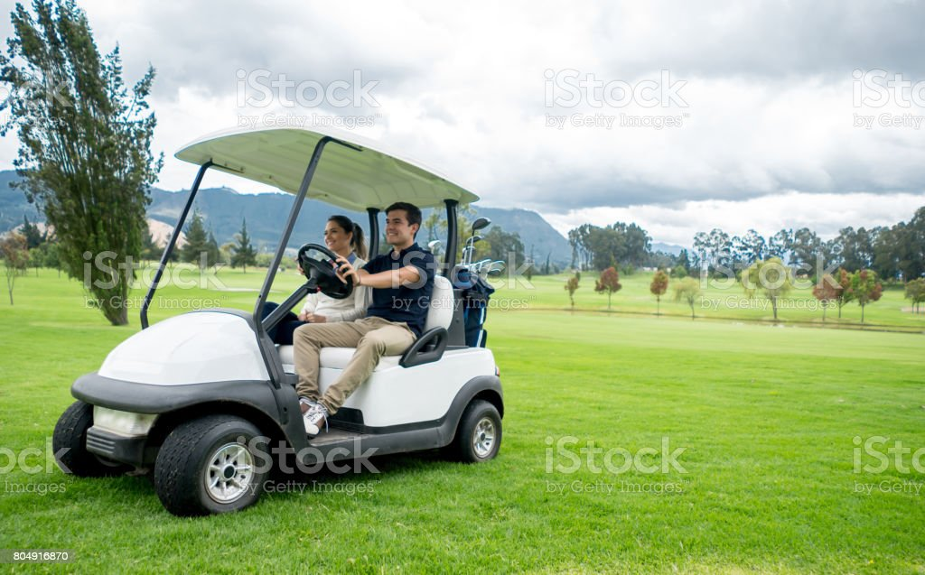 Happy couple of golfers driving a golf cart stock photo