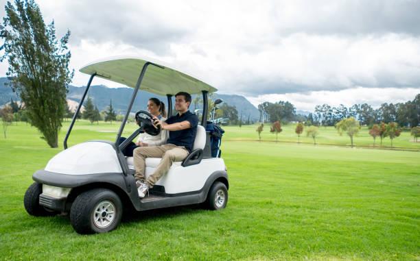 Couple heureux des golfeurs conduire une voiturette de golf - Photo