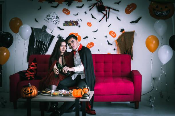 glückliches paar liebe in halloween-kostüm und make-up feiern und trinken bier in halloween-nacht-party - dracula schminken stock-fotos und bilder