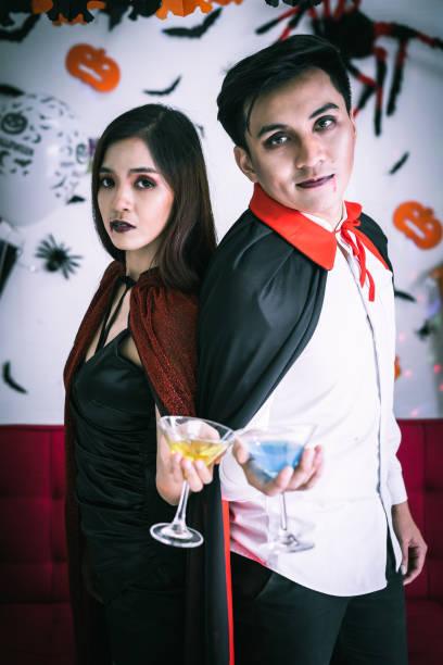 glückliches paar liebe in halloween-kostüm und make-up feiern und halten champagner glas in halloween-nacht-party - dracula schminken stock-fotos und bilder