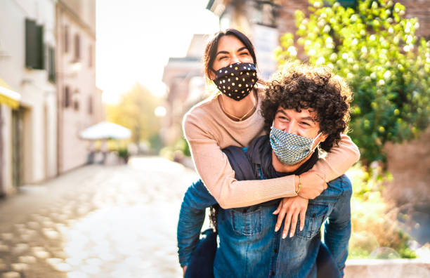 Happy couple of lovers enjoying time outdoor at Valentines day - Handsome guy with nice girl on piggy back moment - New normal love concept with boyfriend and girlfriend together on warm vivid filter stock photo