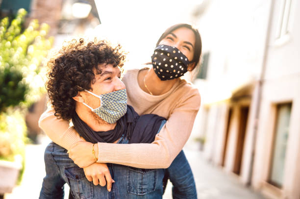 Happy couple of lovers enjoying winter travel time outdoor - Handsome guy with nice girl on piggy back moment - New normal love concept with boyfriend and girlfriend together on warm vivid filter stock photo