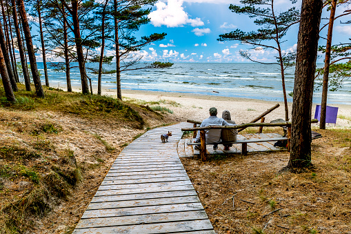 Happy couple of seniors are sitting near a sandy beach of the Baltic Sea