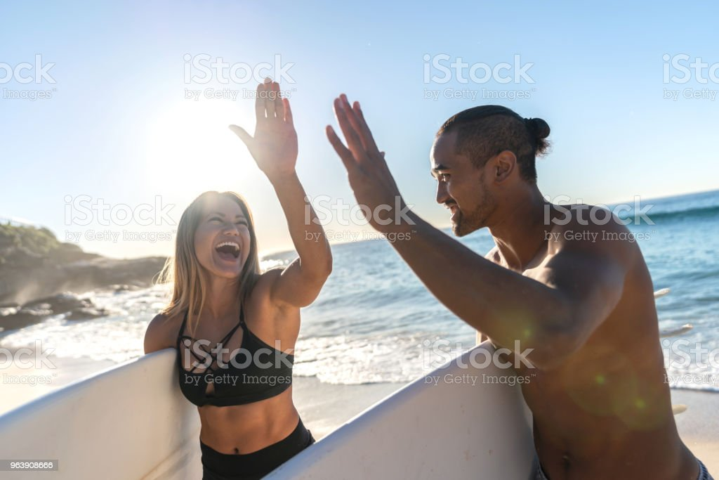 Happy couple of surfers at the beach giving a high-five - Royalty-free Adult Stock Photo