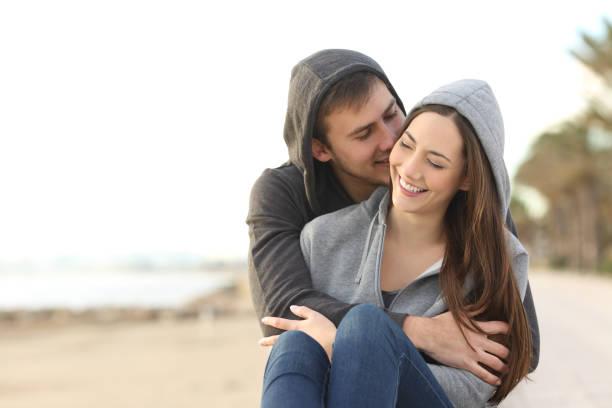 glückliches paar teens flirten am strand - dinge die zusammenpassen stock-fotos und bilder