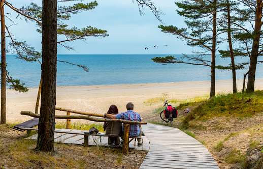 Happy couple of tourists are resting near a sandy beach of the Baltic Sea