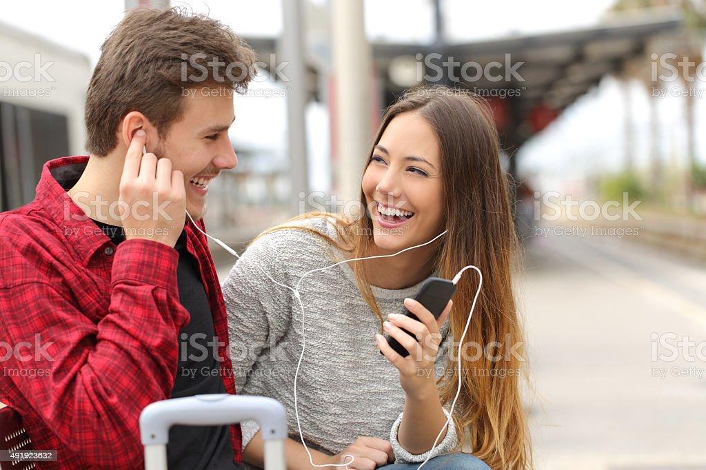 Happy couple of travelers sharing music on holidays stock photo