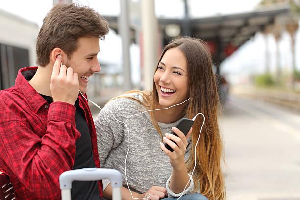 heureux couple de voyageurs partageant la musique sur les jours fériés - écouteurs intra auriculaires photos et images de collection