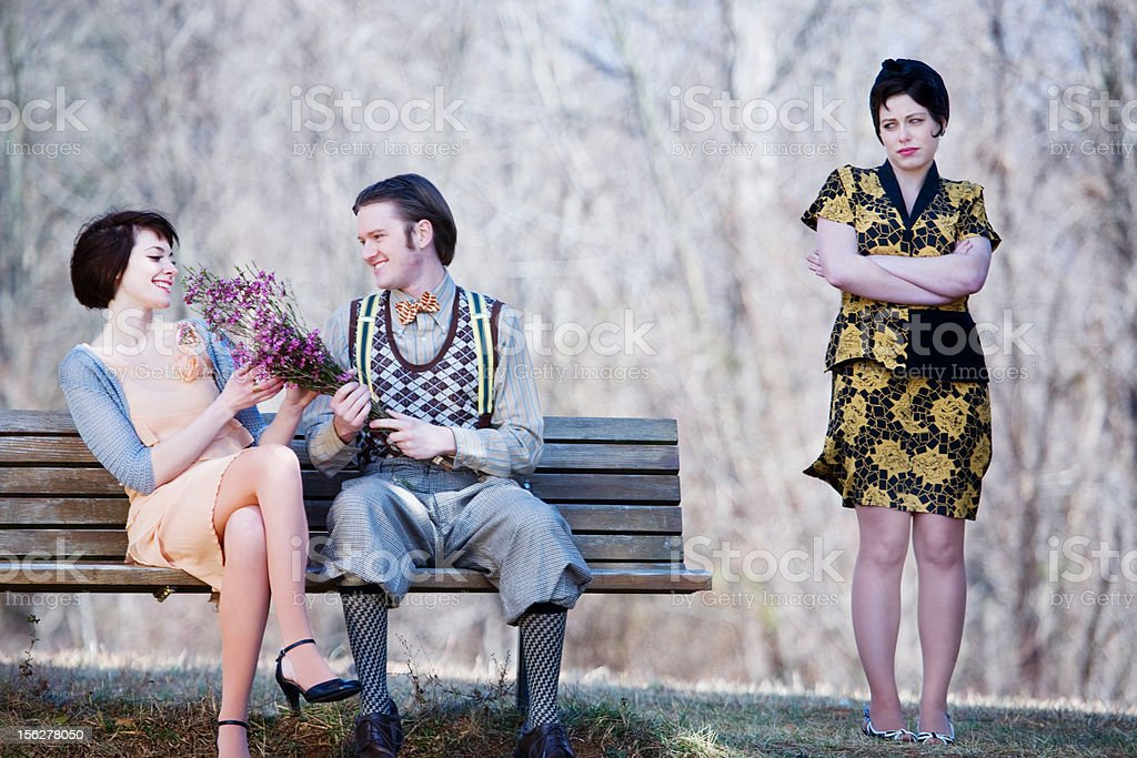 Happy couple on a bench while jealous lady watches royalty-free stock photo