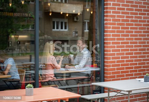 Happy couple on a date at a cafe drinking coffee and smiling while talking - lifestyle concepts