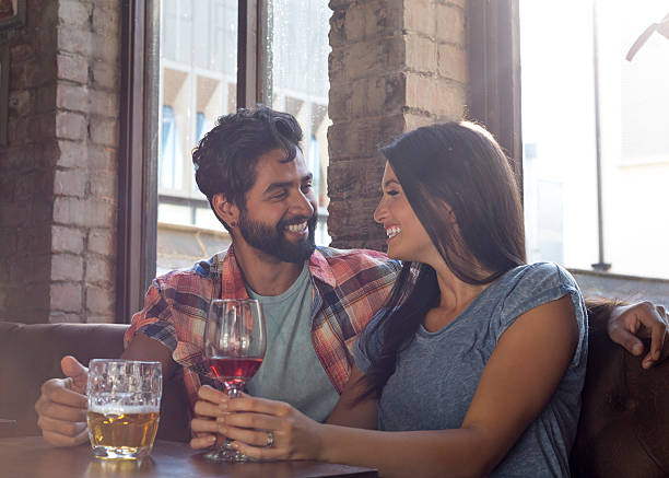 Happy Couple on a Date Happy couple sitting in bar on a date. romance stock pictures, royalty-free photos & images