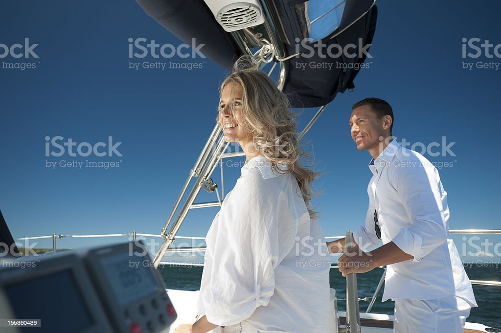 Happy Couple on a sailboat under cloudless sky stock photo