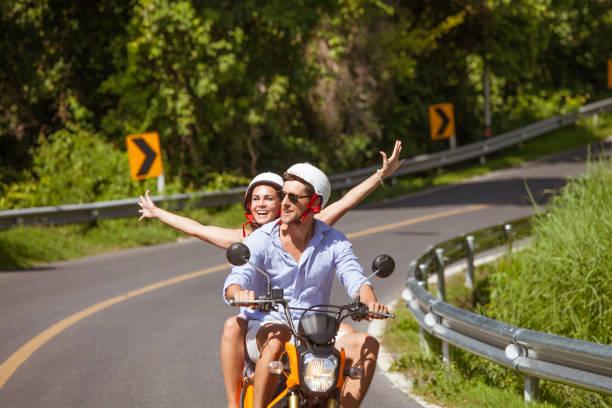Couples heureux sur un scooter - Photo