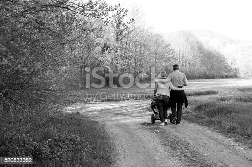 525959168 istock photo Happy couple on a walk with a baby stroller 520833382