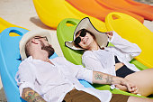 istock Happy couple on chaise-lounges 1206204770