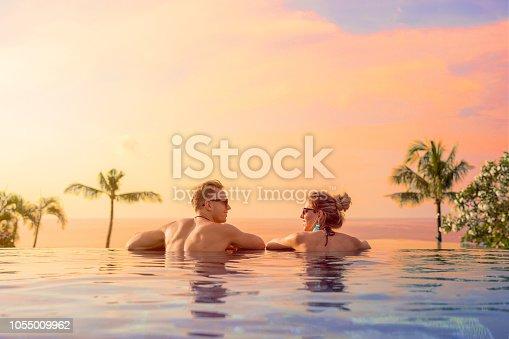 Happy couple enjoying honeymoon in luxury hotel pool