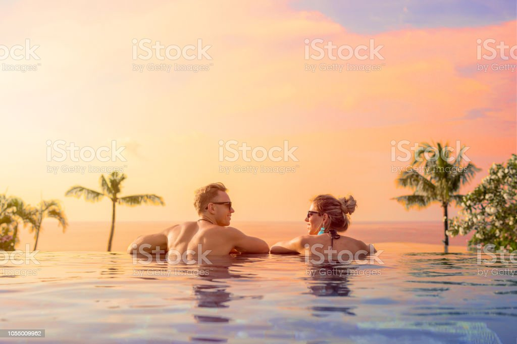 Happy couple on honeymoon in luxury hotel pool stock photo